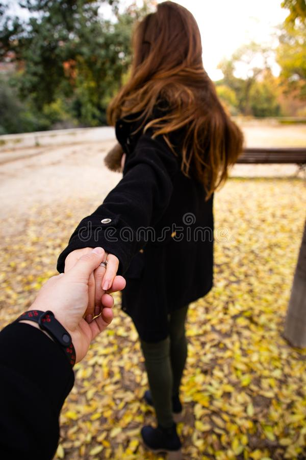 Man holding woman`s hand on fall with leaves on the ground. With copy space stock images