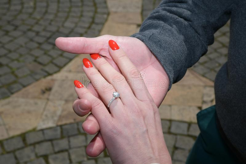 Man holding woman`s hand with engagement diamond ring stock image