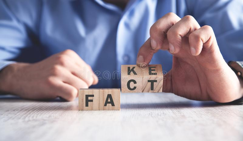 Man holding wooden cubes. Fact or fake. Business concept stock images