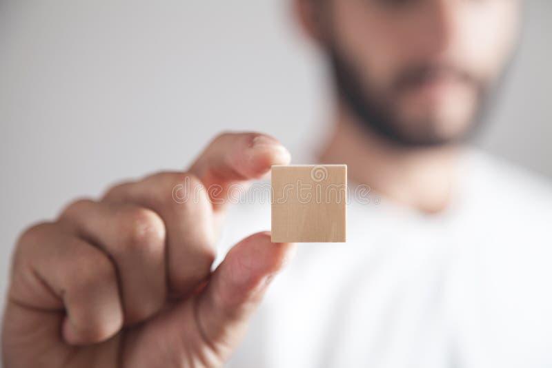 Man holding wooden empty cube stock photo