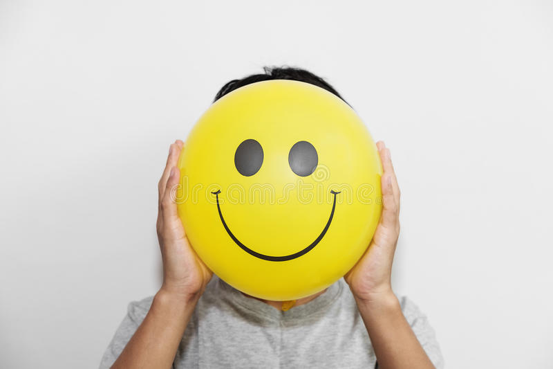 A man holding a yellow balloon with smile face emoticon instead of head. hiding some bad feeling just keep smiling. A man holding a yellow balloon with smile royalty free stock image