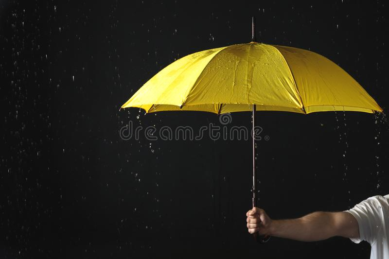 Man holding yellow umbrella under rain against black background stock photo