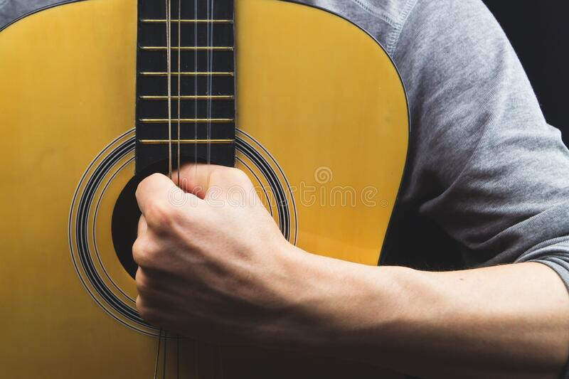 Man holds acoustic guitar. string instrument close up. Man holds acoustic guitar. string instrument stock photography