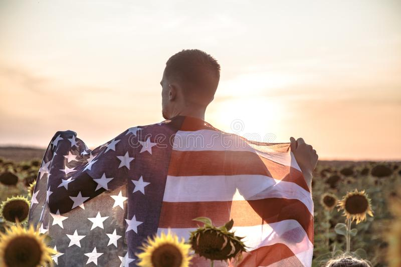 A man holds an American flag at sunset. In a beautiful field. Dressed in white. Patriotic feeling royalty free stock photos