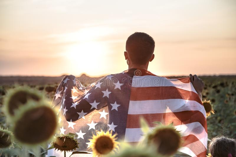 A man holds an American flag at sunset. In a beautiful field. Dressed in white. Patriotic feeling stock image