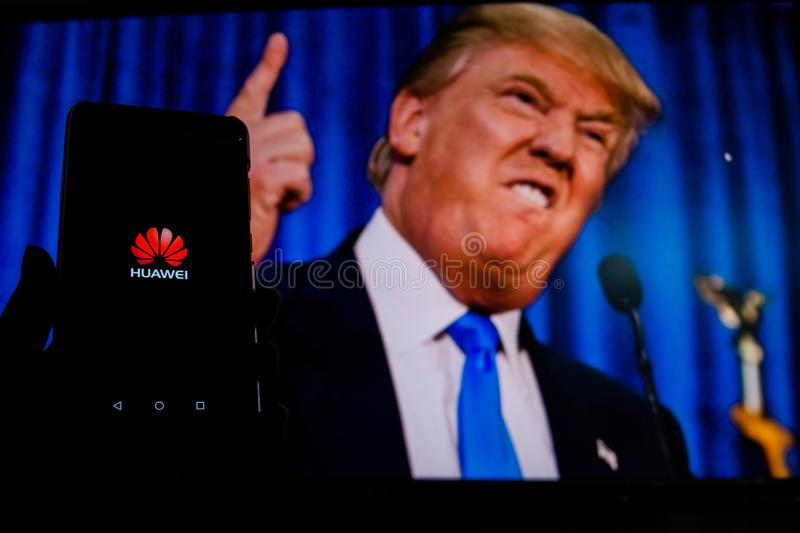 A man holds an android-smartphone that shows the logo for the google play store in front of the picture of Donald Trump stock photo