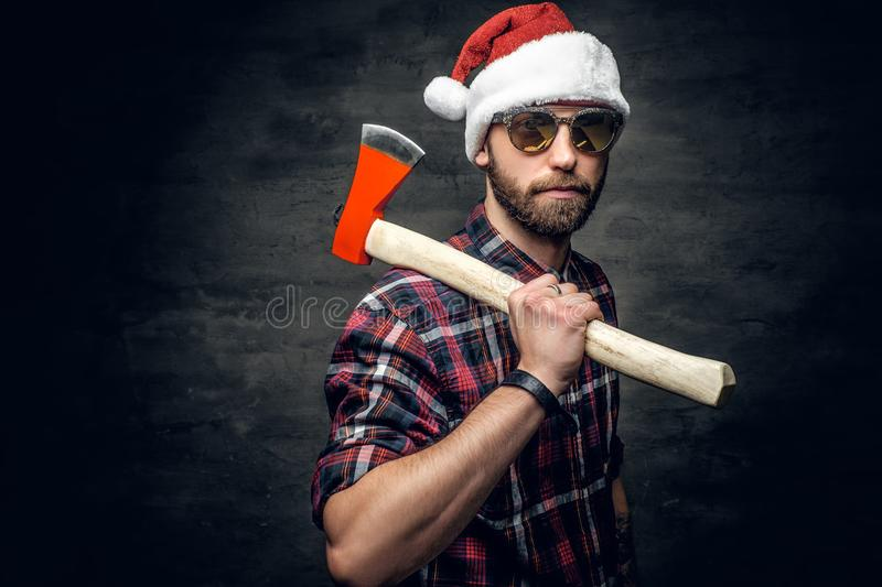 A man holds axe. Portrait of a bearded man wearing Santa`s hat and holds axe royalty free stock images