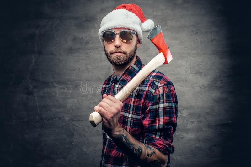 A man holds axe. Portrait of a bearded man wearing Santa`s hat and holds axe royalty free stock photo