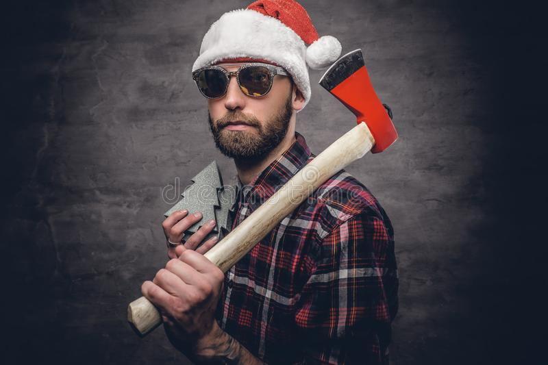 A man holds axe. Portrait of a bearded man wearing Santa`s hat and holds axe royalty free stock photography