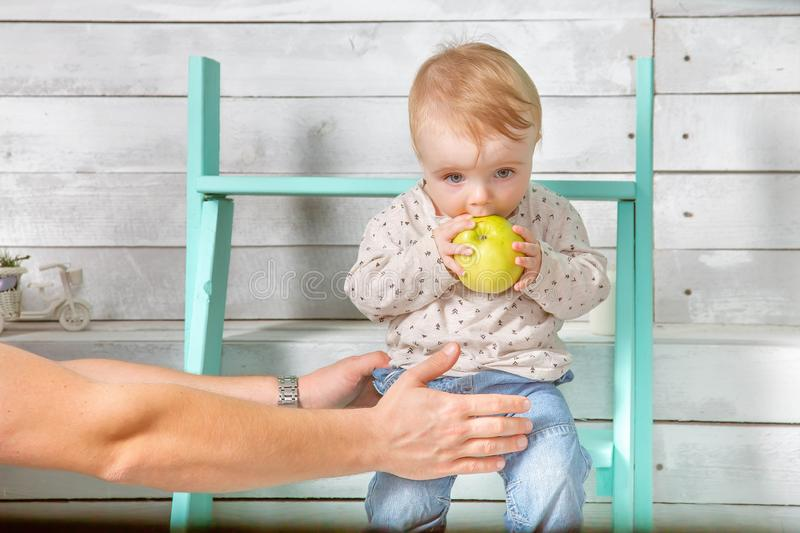 Man holds baby boy who eat big green apple. He both are in jeans and white hoodie. Infant sits on the steps indoor. White wooden. Background royalty free stock photo