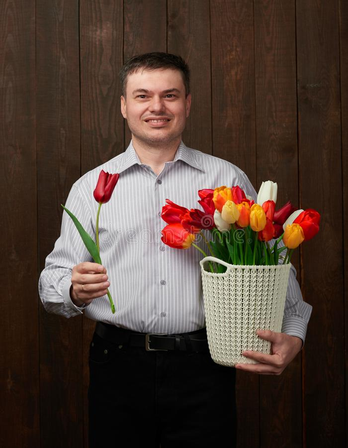 Man holds a basket with flowers stock photo