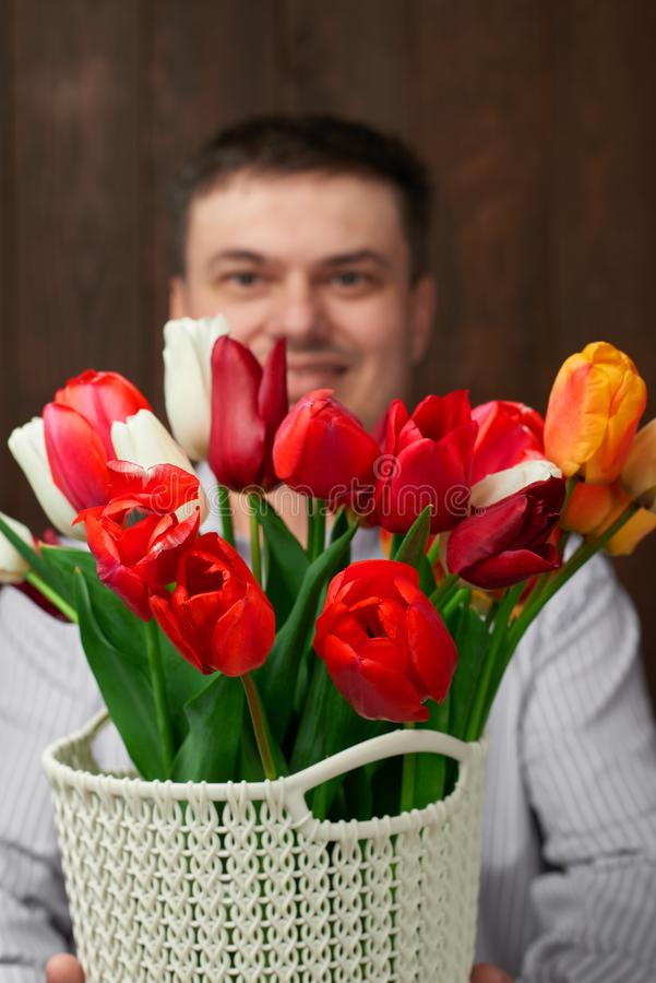 Man holds a basket with flowers stock images