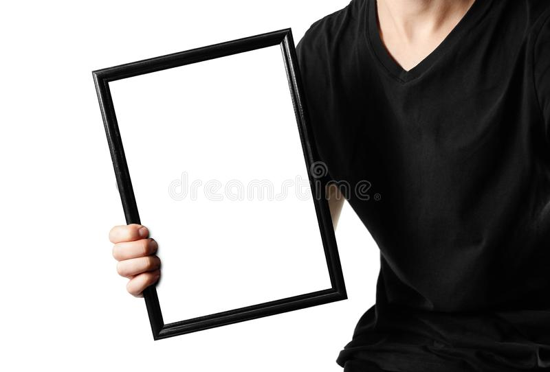 A man holds a black A4 frame. An empty frame with a white background. Close up.  on white background.  stock photography