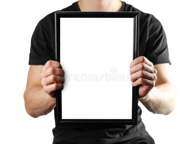 A man holds a black A4 frame. An empty frame with a white background. Close up. Isolated on white background.  stock photos