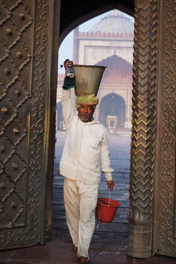 Man holds a bucket at Masjid Jama, Old Delhi, India royalty free stock images
