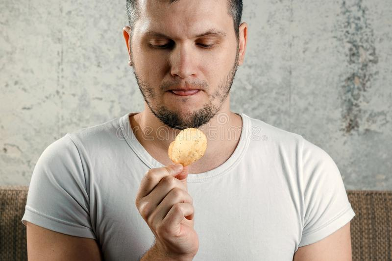 A man holds chips and wants to eat. The concept of harmful food products.  stock image
