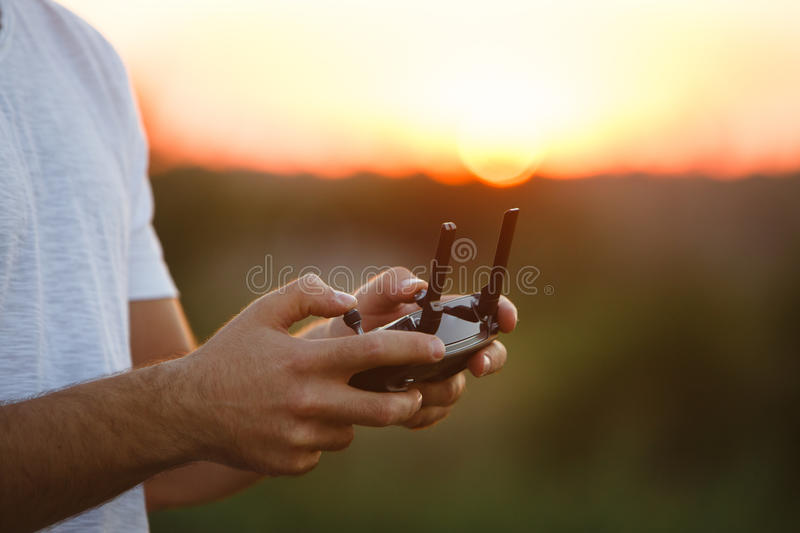 Man holds a drone remote controller in his hands. Close-up of quadrocopter RC during flight. Pilot takes aerial photos. Man holds a drone remote controller in royalty free stock photography