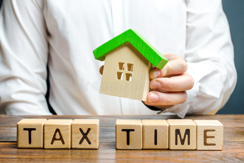 A man holds a figure of a house above the inscription Tax Time. Taxation, income tax. Declaring income, countering the shadow. Economy, digitalization of the royalty free stock photos