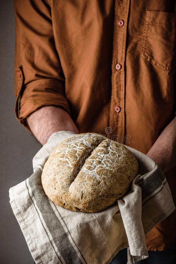 Man holds a freshly baked rye bread royalty free stock images