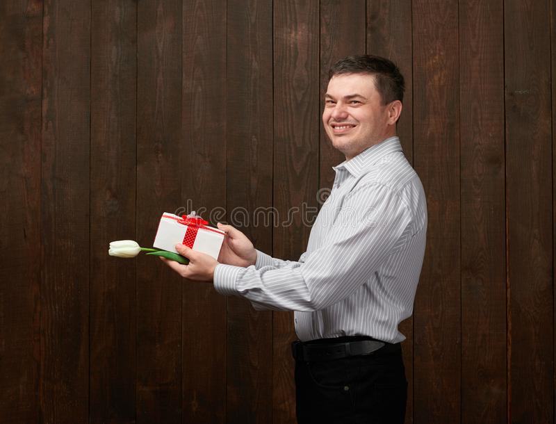 Man holds a gift box and white tulip flower stock images