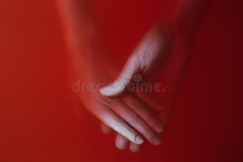 Man holds girl`s hand in water with red paints, concept of love, cover of a thriller or a detective story, mystery art royalty free stock images