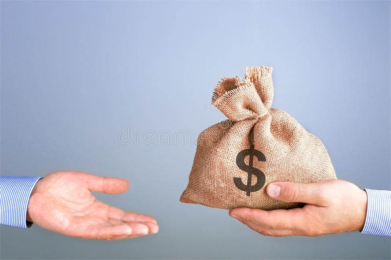 Man holds, gives a bag of money in hand like a bonus. Businessman holding bag of money in hand offering bribe with copy space. Cas stock images