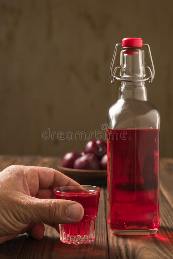 A man holds a glass of plum liqueur near the bottle. Homemade alcoholic drink made from berries plum stock image