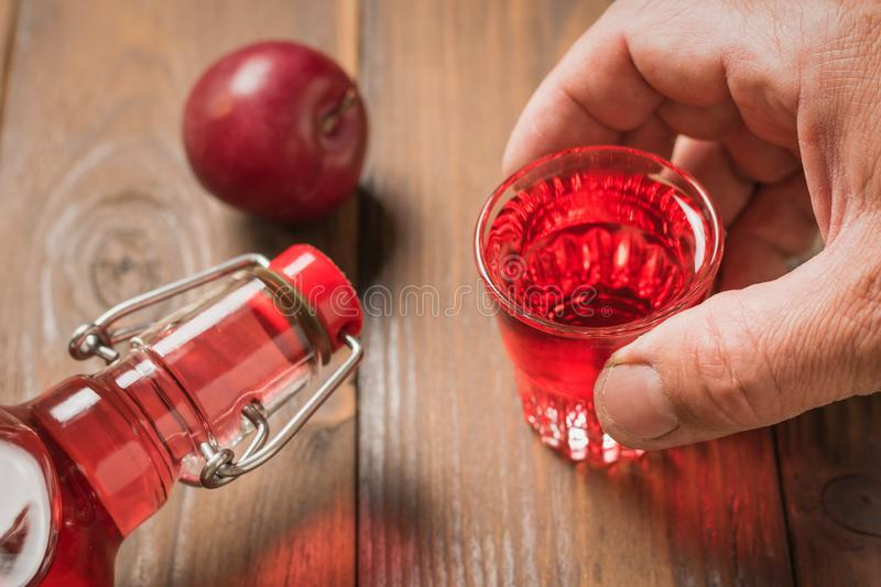 A man holds a glass of plum liqueur over the table. Homemade alcoholic drink made from berries plum stock images