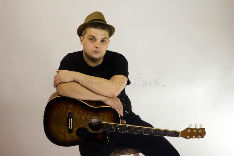 A man holds a guitar on his knee. He`s wearing a black t-shirt, looking at the camera. Hat on head stock images