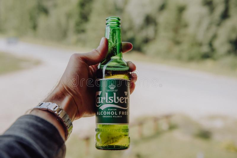 A man holds at hand a bottle of Carlsberg Alcochol Free Organic beer. royalty free stock images