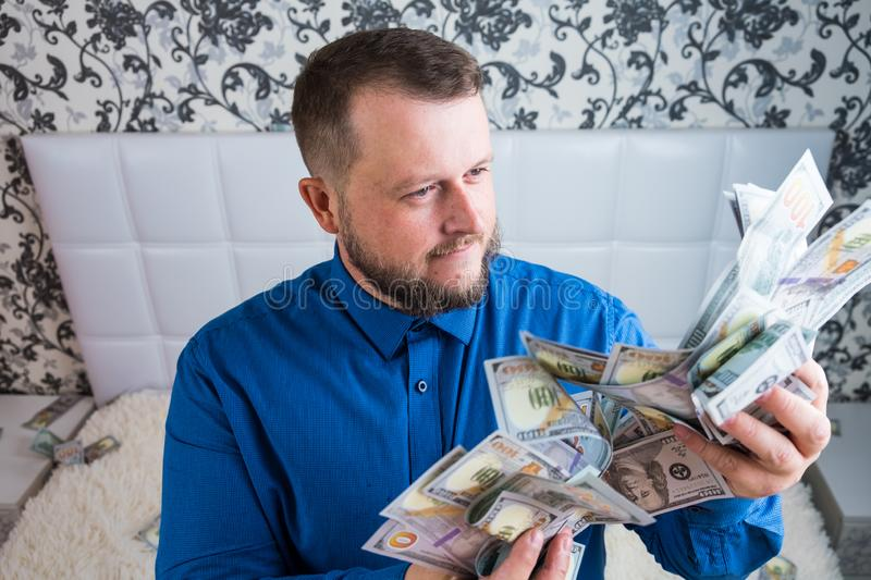 Man holds in hands a large amount of money. A man enjoys great wealth, a lot of banknotes of dollars. stock photos