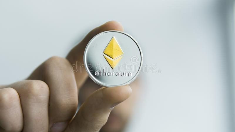 Man holds in hands physical golden silver Ethereum. Cryptocurrency. Profit from mining crypto currencies. Miner with a royalty free stock photography
