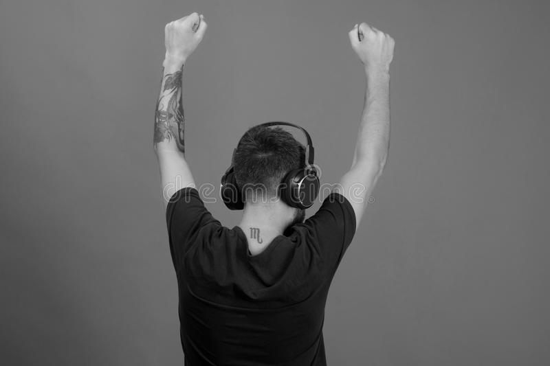 Man holds hands up, turned around on blue background. Man holds hands up, dancing turned around on blue background. Relax and music concept. Singer enjoys music royalty free stock photography