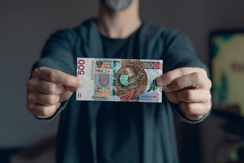 Man holds in hands 500 zlotych banknote  with a face mask against Corona virus infection. Man holds in hands 500 zlotych banknote with a mask on face against royalty free stock photos