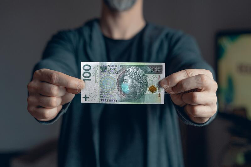 Man holds in hands 100 zlotych banknote  with a face mask against Corona virus infection. Global economy hit by covid19 outbreak and pandemic. Polish economy royalty free stock images