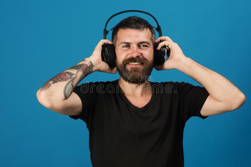 Man holds headphones on blue background. Dj with beard. Wears headphones. Pleasure, music and creative lifestyle concept. Singer with beard and happy face royalty free stock photography