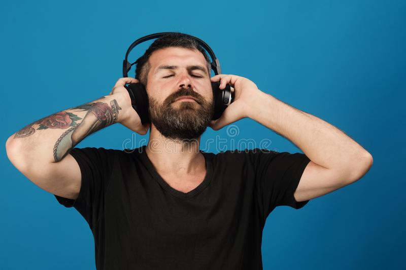 Man holds headphones on blue background. Pleasure, music and lifestyle. Man holds headphones on blue background. Pleasure, music and creative lifestyle concept stock images