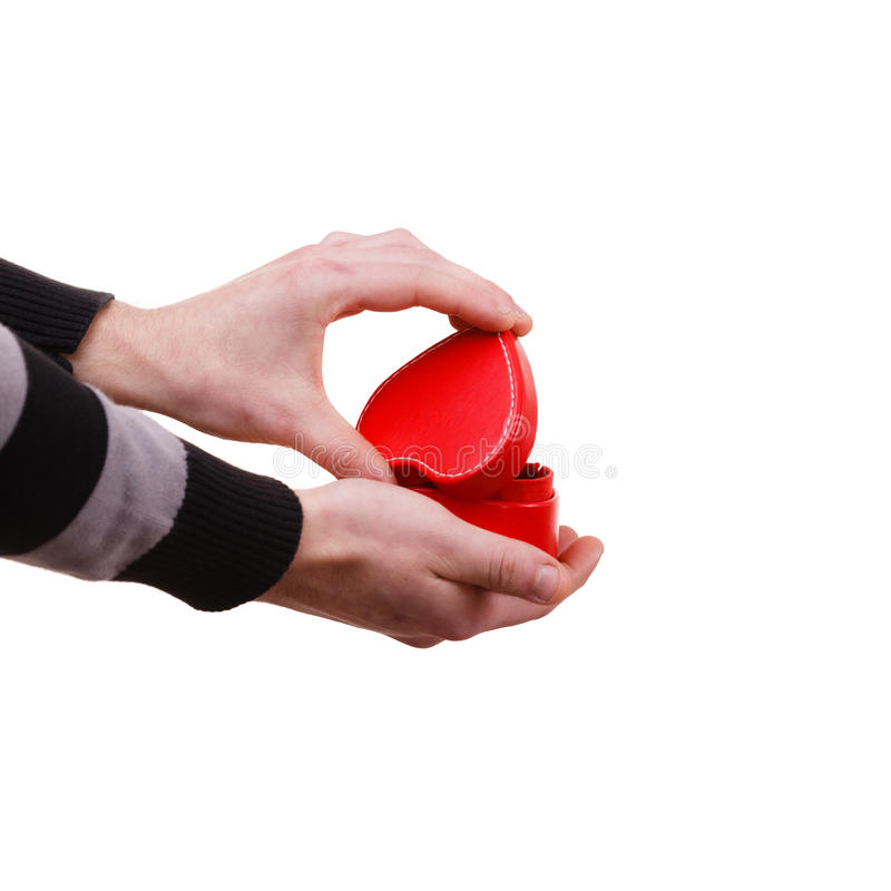 Man holds heart shaped gift box in hand. Holiday valentine day proposing concept. Man holding red heart shaped gift box in hand isolated stock image