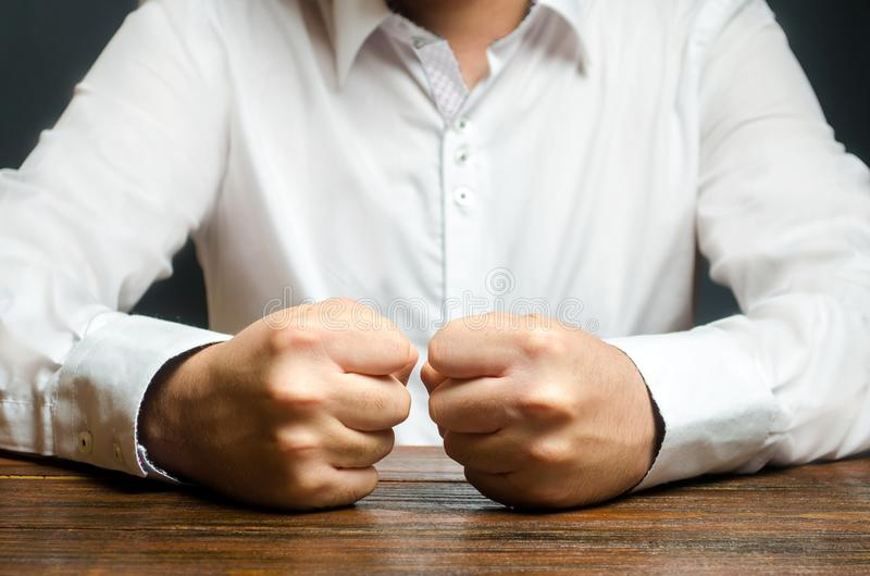 A man holds his closed fists on the table. The end of patience. It is impossible to bear it. An attack of anger, stress. A decisive, emotional gesture stock photography