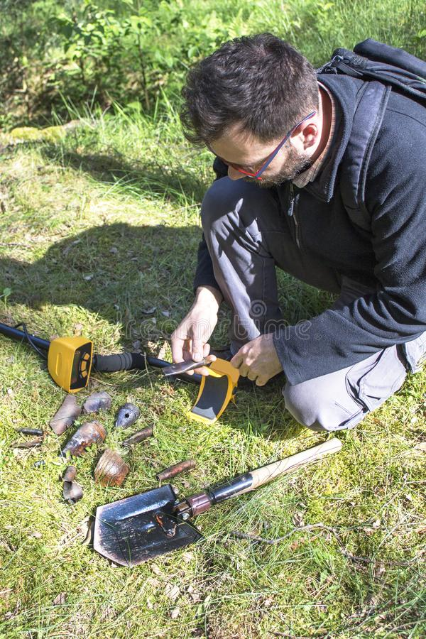 Man holds in his hand an object found in the ground. A metal detector and a shovel lie next to him. The man holds in his hand an object found in the ground. A royalty free stock photography