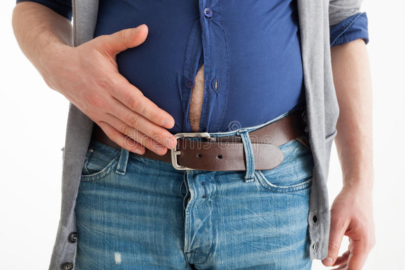 The man holds his hand over his swollen abdomen royalty free stock images