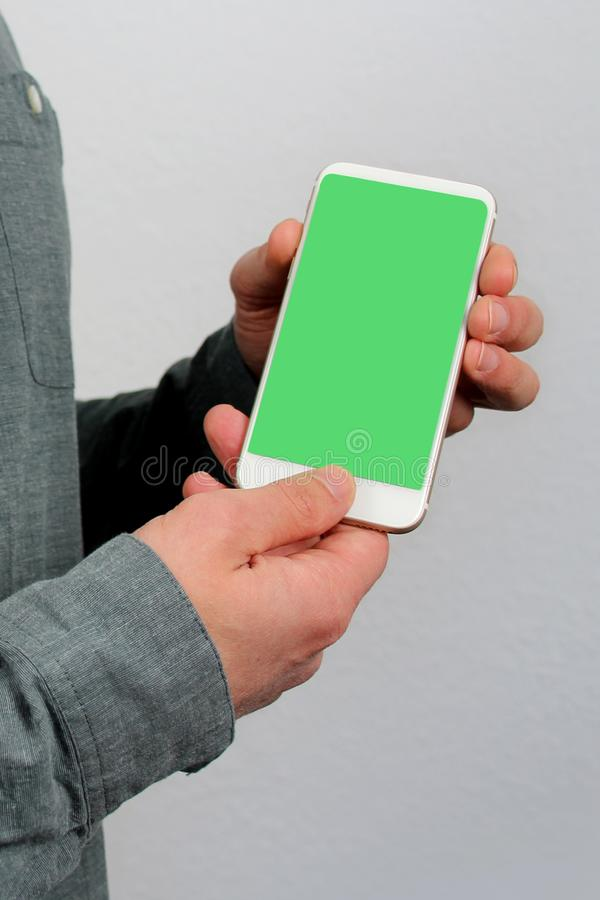 Man holds in his hands a modern phone with green screen in an upright position with a slope, technology concept, close-up, copy. Space stock image