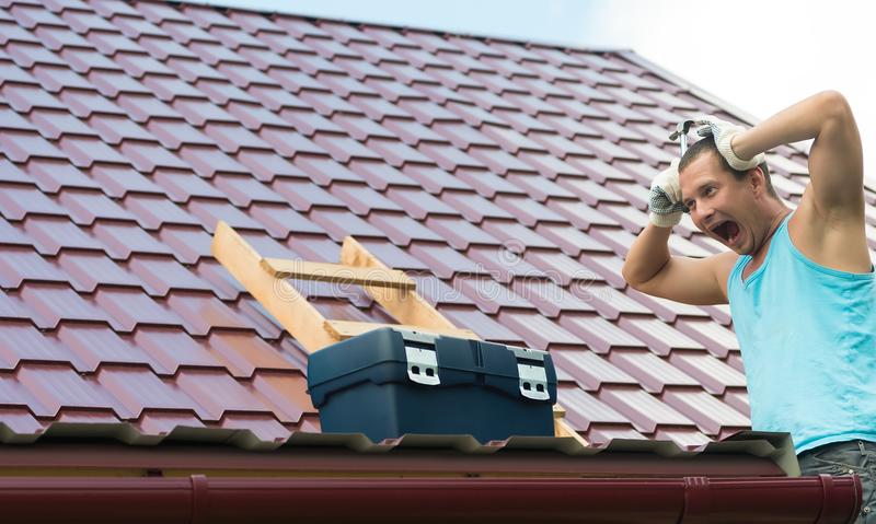 Man holds his head with his hands at the sight of his roof royalty free stock photography