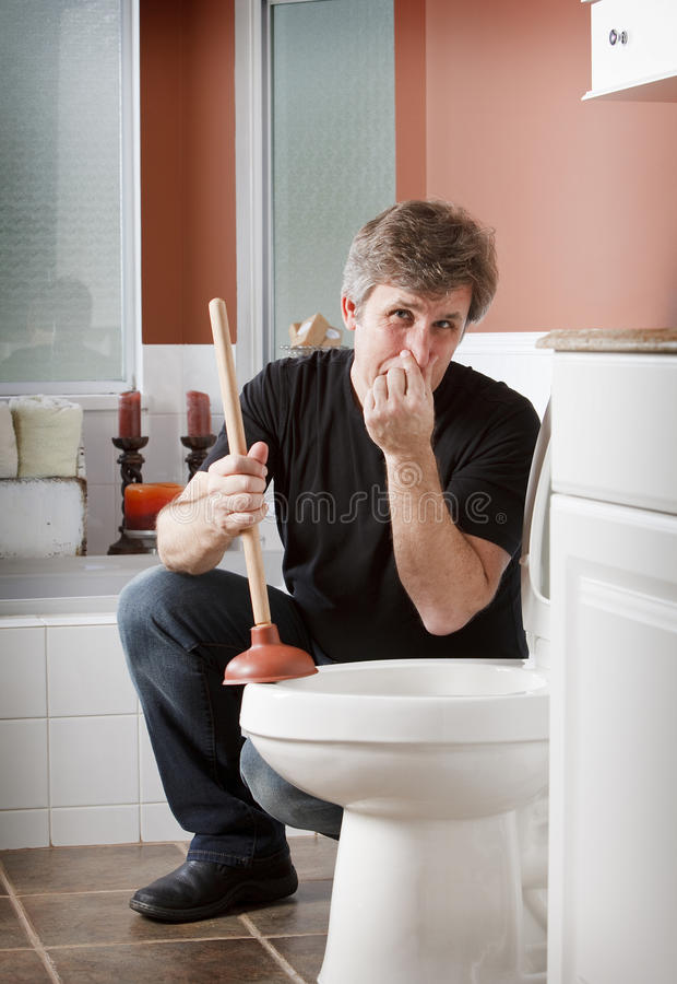 Man holds his nose in bathroom with plunger. A man kneels by the toilet holding a plunger and his breath royalty free stock image