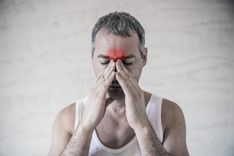 The man holds his nose and sinus area with fingers in obvious pabvious pain from a head ache in the front forehead area. royalty free stock photography