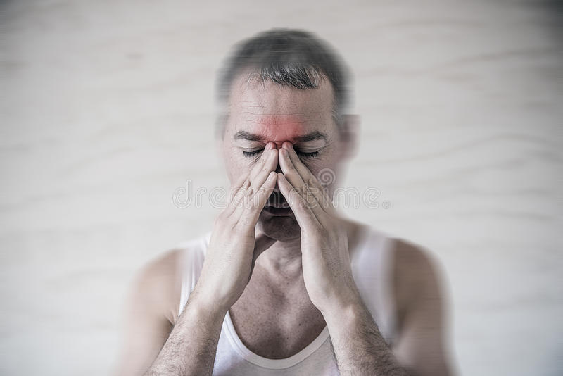 The man holds his nose and sinus area with fingers in obvious pain from a head ache in the front forehead area royalty free stock images