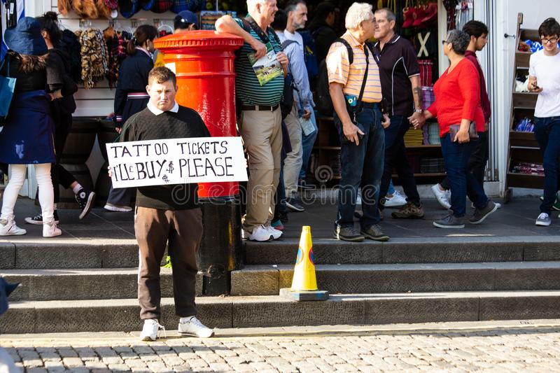 A Man holds a sign offering to buy tickets for the Military Tattoo in Edinburgh during The Fringe Festival 2018. A man holds a home-made sign offering to buy royalty free stock image