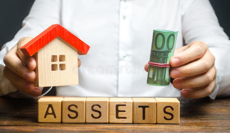 A man holds a house and a bundle roll of Euro over the word Assets. Declaration income and taxation, audit of ownership. Of real estate and cash. Reliable royalty free stock photo