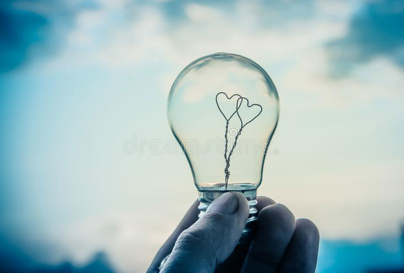 Man holds a light bulb in his hand, inside which there are two hearts against the sky and the sun. The energy of the Sun royalty free stock photos