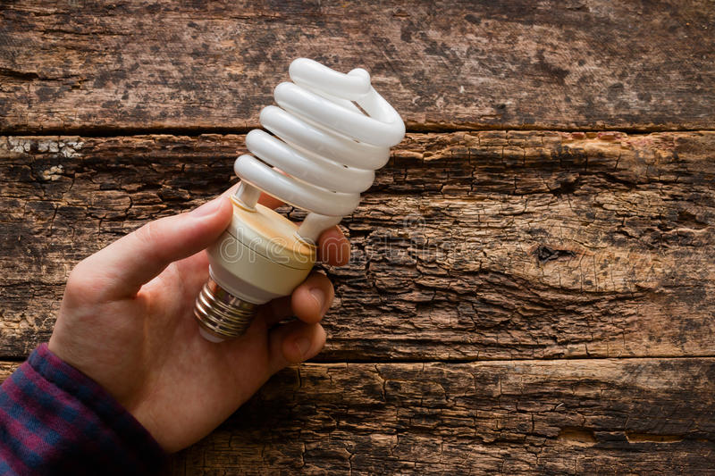 Man holds a light bulb to save energy. On table royalty free stock image
